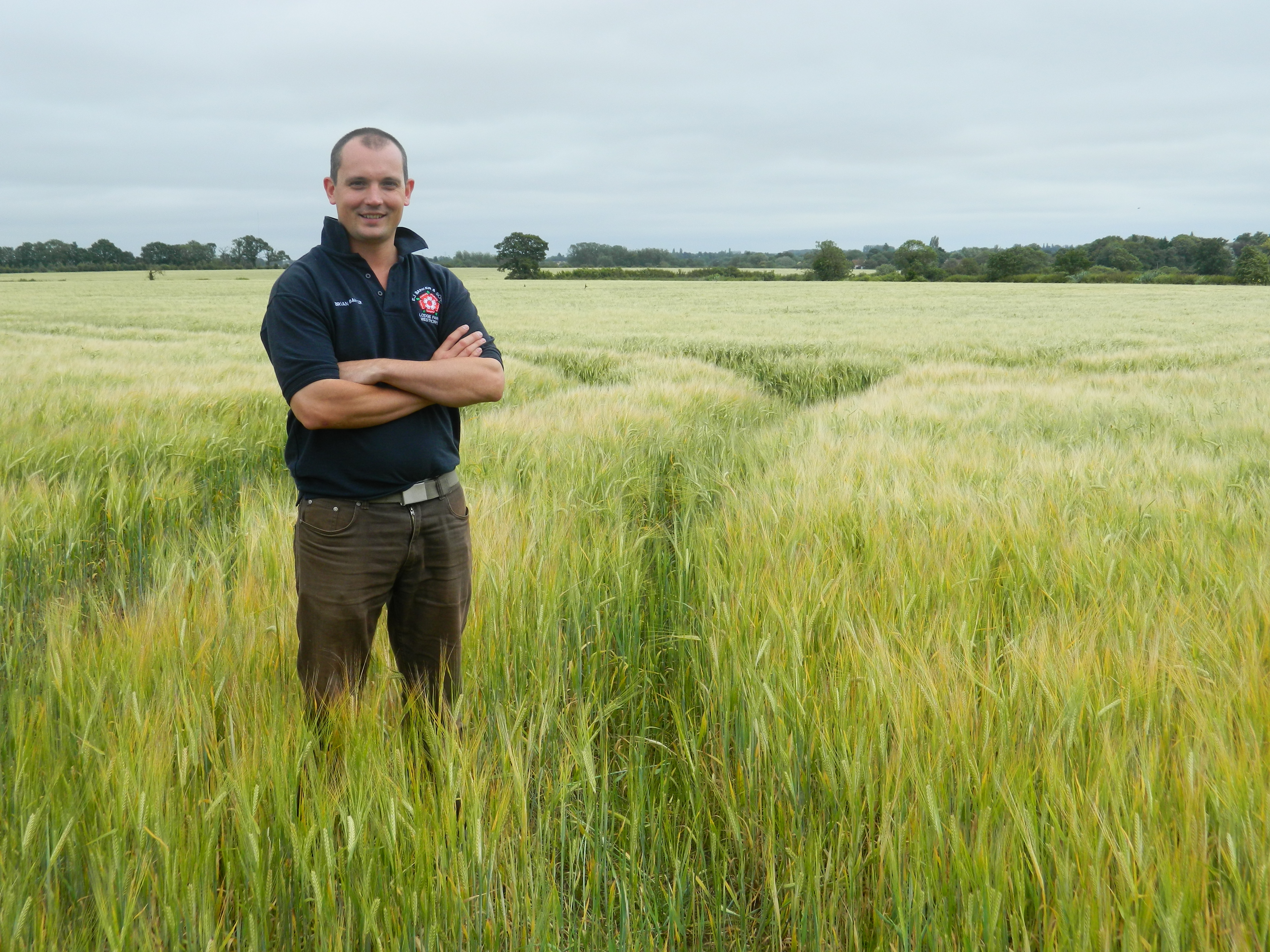 Brian Barker standing in a field of barley