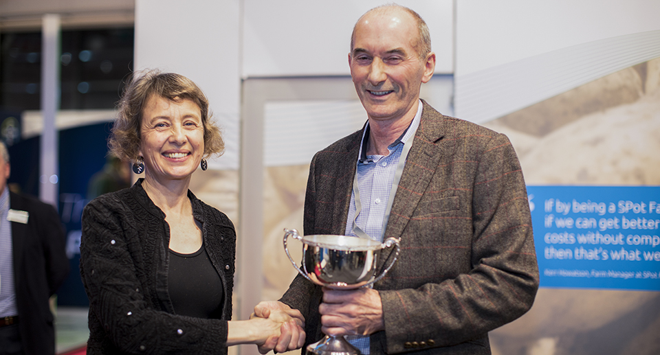 a man and a woman holding a trophy
